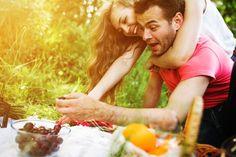 Pareja sonriente comiendo uvas Foto gratis