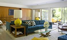 Interesting Mid Century Modern Living Room With Blue Tufted Sofas And Oval Glass Top Table