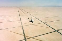 The Space Shuttle Columbia on Rogers Dry lakebed at Edwards AFB after landing to complete its first orbital mission on April 14, 1981. Technicians towed the Shuttle back to the NASA Dryden Flight Research Center for post-flight processing and preparation for a return ferry flight atop a modified 747 to Kennedy Space Center in Florida.