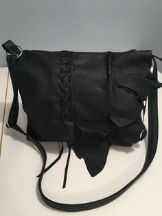 "Soft dark charcoal grey cowhide leather bag with abstract front flap.  Zipper closure on top, braid details on flap, adjustable crossbody strap.  Back outside zipper pocket.  Inside a vibrant retro lining with 5 pockets, including a key clip.  One of a kind bag measures 12""w x 10.5""h x 3""d."