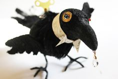 A needle felted form, embellished with textiles. This Raven is a Steampunk Raven and includes Steampunk elements such as watch parts, metal  toy winding keys, crystal, blinking doll eye, brass washer, feathers and a Victorian collar collaged with vintage Italian ephemera.
