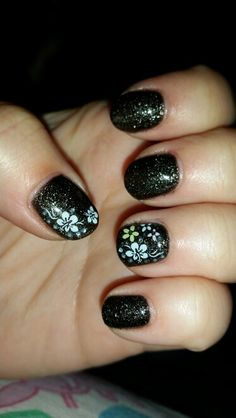 Black sparkle nails with fun flowers.