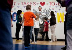 Gym teacher Brian Lossi is strapped with duct tape to the gymnasium wall during an assembly at John L. Hensey School in Washington. Students who raised the most money for the American Heart Association through the Jump Rope For Heart fundraiser took turns covering Iossi with tape until his body was completely covered. The school raised more than $8,000. TAYLOR GLASCOCK/JOURNAL STAR
