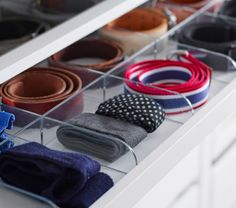 IKEA shallow drawer with clear plastic dividers keeping ties and belts neatly organised.