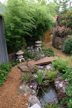 A slab stone bridge and gurgling brook provide a focal point to this oriental garden.
