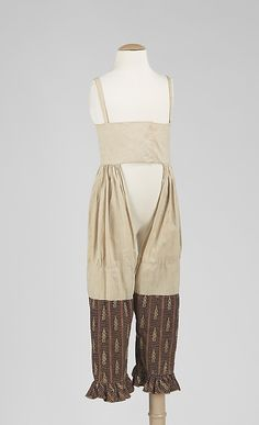 Image 2 of 2:  Dress, 1820-29; American, cotton. The dress and pantalettes seen here are made of a handsome fabric. The pantalettes are particularly interesting because of their construction, which includes shoulder straps. These straps are for convenience and assure the stability of the garment.