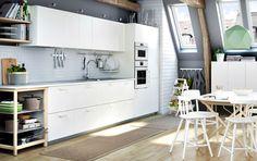 ホワイトのキッチンにグレーのワークトップ。ステンレス製のレンジフード、電子レンジとオーブンを組み合わせています