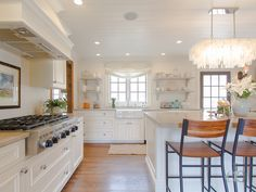 Chic cottage kitchen features a West Elm Large Rectangle Hanging Capiz Chandelier hanging over a white center island topped with cream natural stone lined with wood and iron counter stools.