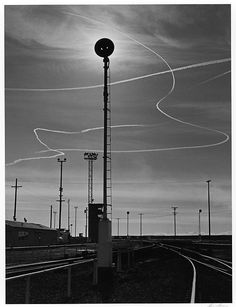 1953 Rails and Jet Trails, Roseville, California [railroad tracks and utility poles, vertical rod with dark disk at top, backlighted; random jet trails] by Ansel Adams Black And White Landscape, Black N White Images, Black White, Ansel Adams Photography, Nature Photography, Dramatic Photography, Ethereal Photography, Inspiring Photography, Roseville California