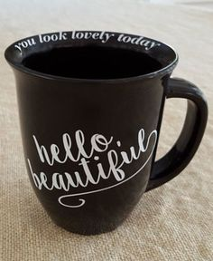 "Large ""HELLO, BEAUTIFUL"" coffee mug, BLACK MUG WITH WHITE LETTERING IN cURSIVE. Around the inside lip of the mug it says you look lovely today""."
