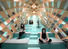 Mexican firm Anagrama has installed a dome of interlocking wood panels at a library in Monterrey, creating bookshelves that arch over a stepped reading area.