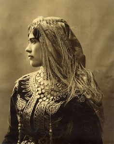 Femme juive d'Algérie 1890 Cette jeune femme porte encore à cette époque la tenue typique des femmes juives d'Algérie, la Gandourah, robe longue , aux borderies fines et dorées.La coiffe à franges est également richement brodée.Plusieurs rangs de perles en collier et les pendentifs en forme de pièces sont également les bijoux de femmes les plus portés à l'époque. Læs mere på: http://www.judaicalgeria.com/pages/photos-d-hier/portraits.html#xFRo4jyD9BGbtQxK.99
