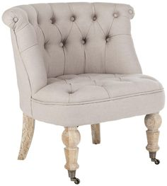 The small-scale Baby tufted chair is inspired by English designs of the Victorian era. Updated with chic upholstery in taupe colored linen, this chair is richly button-tufted and features rolled back