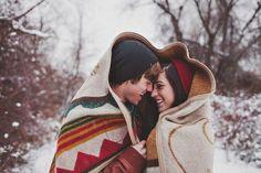 cuddling under a blanket | winter engagement photo