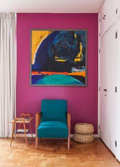 Parede roxa, poltorna azul e obra de arte.