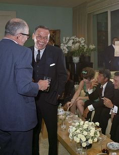 Frank Sinatra talking to Billy Wilder at a wedding party after his marriage to Mia Farrow (1966). Shirley MacLaine and Dean Martin are smoking in the background.