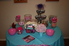 Sweets table with pop rocks, popcorn with food color drizzled on it, suckers, cookies, and a few more sweet treats.