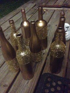 Decorative Bottles : Metallic gold spray paint and I waited about a week to do the glitter… Modge podge adhesive from the craft store and an inch foam paint brush and just sprinkled glitter on them until completely covered -Read More – Wine Bottle Art, Wine Bottle Crafts, Bottles And Jars, Glass Bottles, Glitter Wine Bottles, Painted Bottles, Paint Wine Bottles, Decorated Wine Bottles, Gold Bottles
