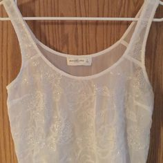 """Abercrombie and Fitch Sheer Unique beaded tank Summer is here and this adorable white sheer tank can go with jeans, jean shorts, colored pants, colored shorts skirts anything you can put up to it it can compliment anything. Dress up or everyday wear. NWOT size S It ended up being to short on me I'm 5'9"""" top is approx 20"""" in length Abercrombie & Fitch Tops Tank Tops"""