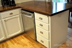 DIY dark butcher block countertops with white cabinets, undermount sink and light wood floor.  Ikea wood.