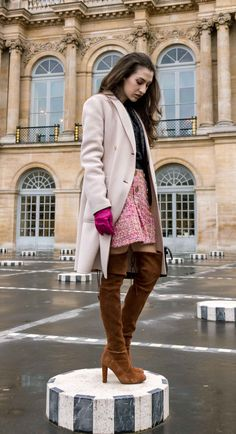 Fashion Blogger Veronika Lipar of Brunette from Wall Street dressed in Stuart Weitzman over the knee boots, Weekend Maxmara coat, Storets pink tweed shorts, black shirt, pink leather gloves and black small bag during Paris fashion week autumn winter 2018/19 standing on Les Colonnes de Buren