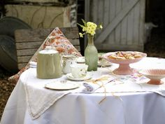 A shabby chic table setup can be as intricate or simple as you like. This outdoor table setting proves that simple layered tablecloths, subtle floral patterns and plain china pieces can be just as beautiful when used modestly.