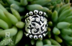This wide sterling silver ring boasts a combination silver beaded and half round edge. Sterling silver overlay scrolls intertwine over a black antique background, creating a simply elegant style.  Perfect for everyday wear! Available by special order only. Learn more at hyosilver.com