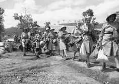 The first contingent of U.S. Army nurses to be sent to an Allied advanced base in New Guinea carry their equipment as they march single file to their quarter on November 12, 1942. The first four in line from right are: Edith Whittaker, Pawtucket, Rhode Island,; Ruth Baucher, Wooster, O.; Helen Lawson, Athens, Tennessee,; and Juanita Hamilton, of Hendersonville, North Carolina