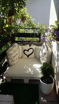 idee deco terrasse, meuble canapé en palettes peint en blanc, avec des matelas et coussins en couleur ivoire, pot blanc avec petit buisson vert, garde-corps en métal noir