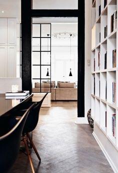 Black framed windows + floor in wood herringbone + built-in bookshelves