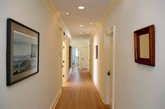 Hallway with recessed lighting, crown moldings and wood floors