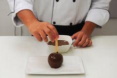 Espere escorrer o excesso de chocolate derretido e coloque a maçã do amor para secar sobre o papel-manteiga. A intenção é evitar que o chocolate grude e rache. Reserve e espere secar por, pelo menos, cinco minutos