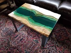 *SOLD* This unique table was passionately handmade by me. The table shown is sold but I can make similar ones upon a custom order request. Made from two live edge figured maple slabs with Baja colored epoxy in-between. Real sand under the epoxy gives the illusion of a river or ocean