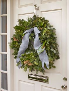 Traditional Home White classic door, with silver door accessories, and  a classic evergreen wreath with a burlap bow for texture.