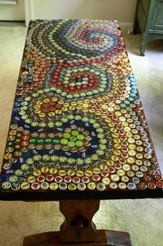 Resin poured over bottle caps on an old coffee table. The product used is called envirotex lite - you can find it at most craft stores, but not always in large enough quantities for doing an entire table (go for the 1/2 gallon or 1 gallon size for that).