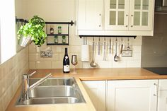 Project Squeeze. Ikea Lindingo kitchen with oak laminate worktop and cream subway tiles.