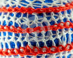 A macro of a glittery bauble covered in red and white crotchet