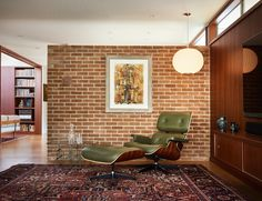 The west brick wall continues to the interior and serves as an accent wall dividing the entry hall from the living room. A corner of the room is furnished with an Eames lounge chair, a Nelson Bubble Lamp, and a Silas Seandel coffee table. Mid Century Chair, Mid Century House, Little Architects, Clad Home, Nelson Bubble Lamp, 1950s House, Modern Style Homes, Maine House, Midcentury Modern