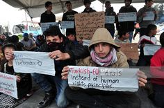 Migrants hold placards reading 'Turkish-EU deals instead of human rights principles', as they protest at the makeshift camp of the Greek-Macedonian border, near the Greek village of Idomeni on March 26, 2016, where thousands of refugees and migrants are stranded by the Balkan border blockade. Greece has begun evacuating migrants from the main Idomeni camp on the Macedonia border, while the flow of refugees arriving on Aegean islands has slowed to a trickle, officials said on March 26, 2016…