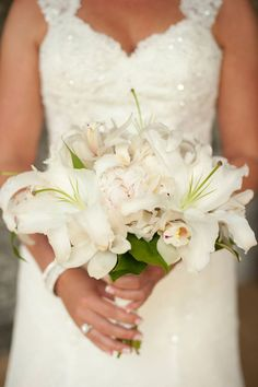 Gorgeous Bridal Bouquet Showcasing: White Casablanca Lilies, White Peonies, White Orchids & Green Foliage••••