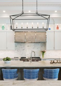 In this kitchen, a custom stove hood crafted by Ruffino Cabinetry with wooden slats and stainless steel banding offers a textural statement alongside brilliant glass collectables. Lee Industries' counter stools pull up to the breakfast bar for family and guests to enjoy early morning culinary delights.