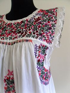 Mexican dress, pinks/reds/purples on white.