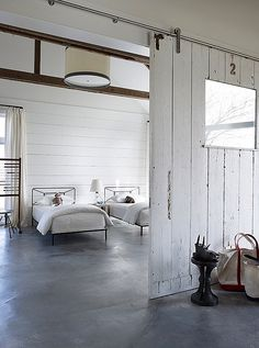 Light-filled country bedroom with twin beds and shiplap walls inside a converted barn.