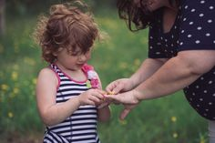 Young daughter putting flower on expecting mother's wedding ring outside in a field during family maternity photography session by Kasey Wallace Photography in Corunna, Indiana, www.kaseywallacephoto.com