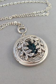 This antique silver locket has a beautiful leafy ivy branch adorned to the front of this silver round locket. In the center sits a vintage emerald green stone, that has been framed in an antiqued silver setting. A sweet antiqued silver floral connector has been added to this locket