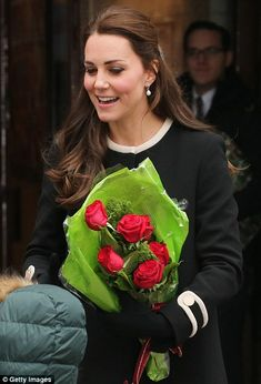 Quite the welcome: Kate's flowers set off her outfit as she moved through the crowds ahead of the activities with the children inside.
