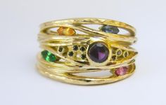 18ct Fairtrade yellow gold 'river' ring, with purple, orange, pink and blue sapphires and a tsavorite garnet, finished with a peppering of black diamonds, in hammered finish Zoe Pook
