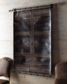 At Horchow, tapestry with the look of tooled leather. Could be a cool masculine headboard, horizontal or vertical.