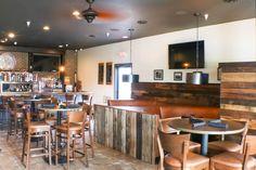 Prairie House bar with wooden barn door booths.