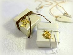 Clasic ivory or white favor boxes decorated with gold olive twig or pomegranate charm. Each box is wrapped with brown or white suedete cord and finished with olive twig or pomegranate gold charm. You may costumize colors of box and suede cord. Dimensions: 8 x 8 x 4,5 cm. Five sugared